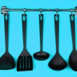 Black kitchen utensils on silver hooks, on blue background — Stock Photo #31785153