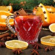 Stock Photo: Fragrant mulled wine in glass with spices and oranges around on wooden table