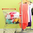 Shopping cart with clothing, on color wall background — Stock Photo #31789021