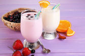 Delicious milk shakes with orange and blackberry on wooden table close-up — ストック写真