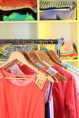 Variety of clothes on wooden hangers on shelves background — Stockfoto