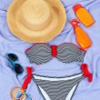 Swimsuit and beach items on purple background — Stock Photo