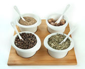 Assortment of spices in white bowls, on wooden board, isolated on white — Stock Photo