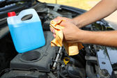 Motor mechanic cleaning his greasy hands after servicing car — Stock Photo