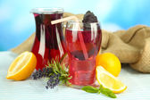 Red basil lemonade in jug and glass, on wooden table, on bright background — Stockfoto