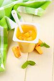 Saboroso iogurte com pedaços de fruta fresca, na cor de fundo de madeira — Foto Stock