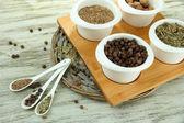 Sortiment av kryddor i vit skedar och skålar, på trä bakgrund — Stockfoto