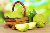 Osage Orange fruits (Maclura pomifera) in basket, on wooden table, on nature background — Stock Photo