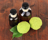 Osage Orange fruits (Maclura pomifera) and medicine bottles, on wooden background — Stock Photo