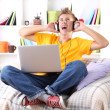 Young man relaxing on sofa with laptop — Stock Photo