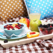 Oatmeal in plate with berries on napkins on wooden tray on bad — Stock Photo