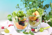 Fruit salad in glasses, on wooden table, on bright background — Stock Photo