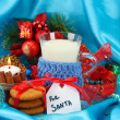 Cookies for Santa: Conceptual image of ginger cookies, milk and christmas decoration on blue background — Stock Photo #31894573