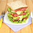Huge sandwich on wooden table, on bright background — Stock Photo #31895403