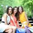 Three beautiful young woman with shopping bags in park — Stock Photo