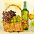 Ripe grapes in wicker basket, bottle and glass of wine, on light background — Stok Fotoğraf #31898491