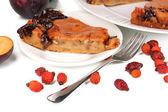 Gustosa torta sul piatto con prugne isolato su bianco — Foto Stock