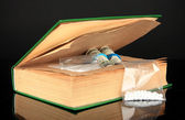 Narcotics in book-hiding place isolated on black — Stock Photo