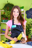 Beautiful girl florist with flowers in flowers shop — ストック写真