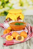 杏酱在玻璃碗和新鲜的杏子,木桌上,在明亮的背景上 — 图库照片