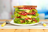 Huge sandwich on wooden table, on light background — Stock Photo