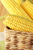 Crude corns in basket on napkin on wooden table — Stock Photo