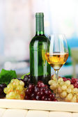 Wine bottle and glass of wine on tray, on bright background — Stock Photo