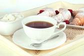 Tasse tee mit kuchen auf hölzernen tablett auf tisch im zimmer — Stockfoto