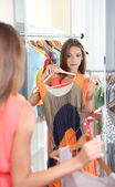 Beautiful girl trying dress near mirror on room background — Stock Photo