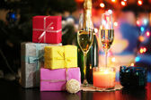 Glasses of champagne and gifts on bright background — Stock Photo