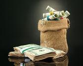 Dinero en bolsa en el fondo de color oscuro — Foto de Stock