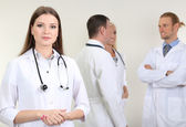 Doctor standing in front of coworkers on grey background — Stock Photo