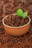 Chicchi di caffè in tazza su fondo in legno — Foto Stock