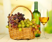 Ripe grapes in wicker basket, bottle and glass of wine, on light background — Foto Stock