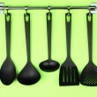 Stock Photo: Black kitchen utensils on silver hooks, on green background