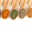 Assortment of spices in wooden spoons, isolated on white — Stock Photo #31901525