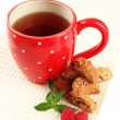 Cup of tea with cookies and raspberries isolated on white — Stock Photo