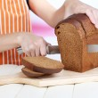 Stock Photo: Cutting bread on wooden board on wooden table on bright background