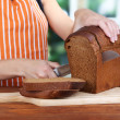 Stock Photo: Cutting bread on wooden board on wooden table on window background