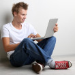 A handsome young man with laptop on grey background — Stock Photo
