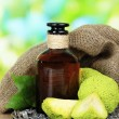 Osage Orange fruits (Maclurpomifera) and medicine bottle, on wooden table, on nature background — Stock Photo #31904695