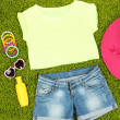 Top, shorts and beach items on bright green background — Stock Photo