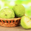 Osage Orange fruits (Maclurpomifera) in basket, on wooden table, on nature background — Stock Photo #31905245
