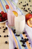 Delicious milk shakes with strawberries and peach on wooden table close-up — Stockfoto
