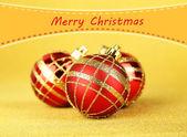 Christmas balls on yellow background — Stock Photo