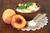 Sour cheese and fresh peaches,on wooden table background — Stock Photo