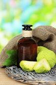 Osage Orange fruits (Maclura pomifera) and medicine bottle, on wooden table, on nature background — Stock Photo
