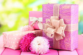 Gifts and flowers, on nature background — Stock Photo