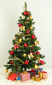Decorated Christmas tree with gifts on grey wall background — Stock Photo
