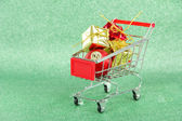 Christmas gifts in shopping trolley, on green shiny background — Stock Photo